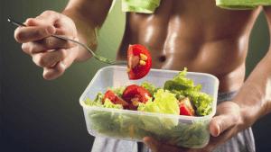 homem sarado comendo salada no pote
